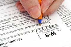 Person hand with pen filling in form W-9 Stock Image