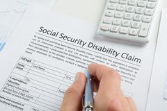 Person hand with pen filling social security disability form. Close-up Of Person Hand With Pen And Calculator Filling Social Security Disability Claim Form Stock Photo