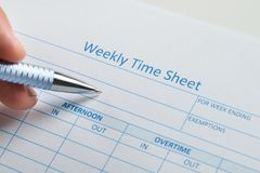 Person hand with pen over weekly time sheet. Close-up Of Person Hand With Pen Over Blank Weekly Time Sheet Royalty Free Stock Photo