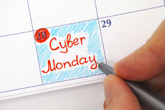 Person hand with pen writing Cyber Monday in calendar. Person hand with red pen writing reminder Cyber Monday in calendar Royalty Free Stock Photography