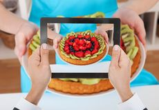 Person hand photographing fruit tart Royalty Free Stock Photos