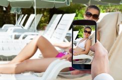 Person hand photographing woman on lounge chair Royalty Free Stock Photos