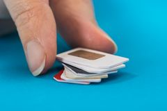 Person hand placing stack of sim card Royalty Free Stock Images
