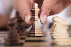 Person Hand Playing Chess And que guarda o rei Chess Piece imagem de stock royalty free