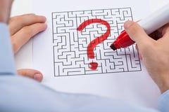 Person Hand With Question Mark auf Labyrinth lizenzfreie stockbilder