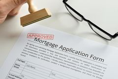 Person hand with stamp and approved mark on mortgage application Royalty Free Stock Photo