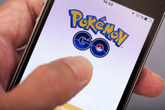Person hand starting Pokemon Go application on apple iPhone5s Royalty Free Stock Photos
