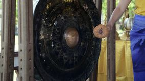 Person hand striking small Asian gong close up. Static shot of miniature gong in focus with shallow depth of field stock video