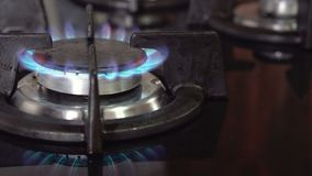 Person hand switching on kitchen stove burner. Blue gas flames, Burning gas . stock video footage
