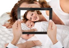 Person hand taking photo of mother with baby Stock Photos
