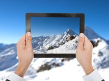 Person hand taking photo of snowy mountain. Close-up Of Person Hand Taking Photo Of Snowy Mountain Stock Photo