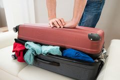 Person hand trying to close suitcase Royalty Free Stock Photos
