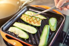 Person hand with tweezers frying organic zucchini on grill iron pan. Close-up grilled sliced vegetables cooking process for vegan stock photos