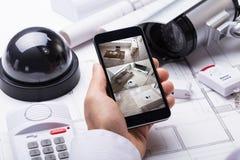Person Hand Using Home Security system på mobilephonen royaltyfri bild