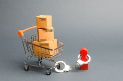 A person is handcuffed to a bunch of boxes a on a supermarket cart. The concept of dependence on shopping and buying new things. Shopaholic, psychological royalty free stock photography