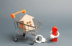 A person is handcuffed to a house on a supermarket cart. Financial dependence, unavailable housing for young families. Freeze of. Property. The concept of a royalty free stock image