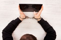 Person in Handcuffs. Hold a Tablet Computer on the Table closeup Royalty Free Stock Photos