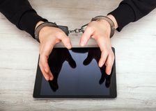 Person in Handcuffs. Hold a Tablet Computer on the Table closeup Royalty Free Stock Image