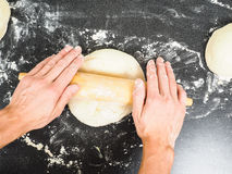 Person handling a dough with wooden rolling pin Royalty Free Stock Photos