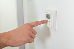 Person Hands Adjusting Temperature On un termóstato de Digitaces Imágenes de archivo libres de regalías