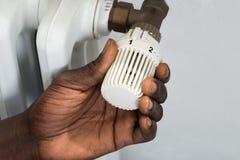 Person Hands Adjusting Thermostat Radiator Fotos de archivo