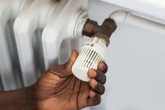 Person Hands Adjusting Thermostat Radiator Imagen de archivo