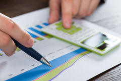 Person Hands Analyzing Financial Report. Close-up Person Hands Analyzing Financial Report With Calculator Stock Photo