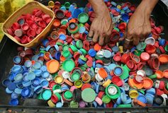 Person Hands on Assorted-color Plastic Lid Lot Royalty Free Stock Photo