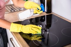 Person Hands Cleaning Induction Stove In Kitchen stock photography