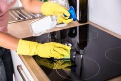 Person Hands Cleaning Induction Stove na cozinha fotografia de stock
