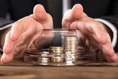Person Hands Covering Coins In-Kom royalty-vrije stock foto's