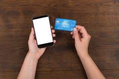 Person Hands With Credit Card e telefone celular imagens de stock