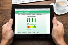 Person Hands With Digital Tablet, der Kreditscore zeigt Stockfotos