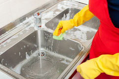 Person hands with gloves cleaning the kitchen sink. Person hands in yellow gloves cleaning the kitchen sink with disinfectant royalty free stock image
