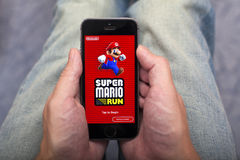 Person hands holding iPhone with Super Mario Run game app. Tambov, Russian Federation - December 17, 2016 Person hands holding iPhone with Super Mario Run game Stock Images