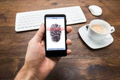 Person Hands Holding Mobile Phone con el uso de la huella dactilar Foto de archivo libre de regalías