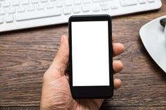 Person Hands Holding Mobile Phone en el escritorio Imagenes de archivo
