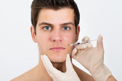 Person Hands Injecting Syringe On Man Face. Close-up Of Person Hands Injecting Syringe On Young Man Face royalty free stock photos