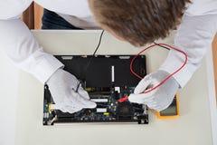 Person Hands With Laptop Motherboard et multimètre images stock