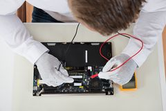 Person Hands With Laptop Motherboard And Multimeter Stock Images