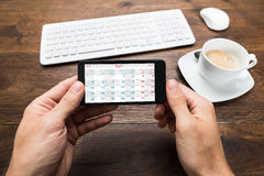 Person Hands With Mobile Phone die Kalender tonen stock foto's