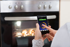 Person Hands With Mobile Phone In Front Of Oven stock image