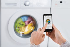 Person Hands Operating Washing Machine com telefone celular Foto de Stock