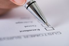Person hands with pen over customer survey form Stock Photo