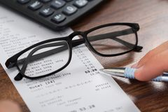 Person hands with pen over receipt and eyeglasses Stock Images