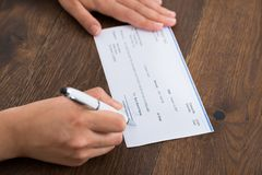Person Hands Signing Cheque Fotografía de archivo libre de regalías
