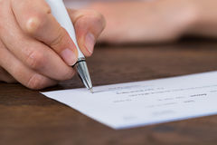 Person Hands Signing Cheque Royalty Free Stock Photo