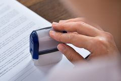 Person Hands With Stamper And Document Stock Photo