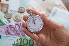Person Hands With Stopwatch Over Money Stock Image