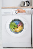 Person Hands Turning Button Of Washing Machine Stock Photo